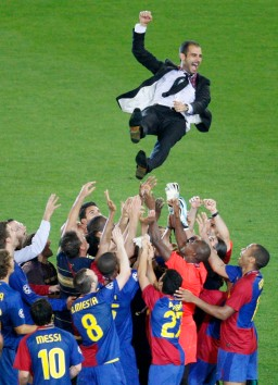 Barcelona players toss their coach Guardiola into the air after their Champions League final soccer match victory against Manchester United in Rome